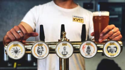 Photograph of a person standing behind a line of German craft beer pumps