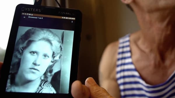 Still from a student film, showing the a person's shoulders, wearing a stripy top, holding a phone with an image of a woman on it.