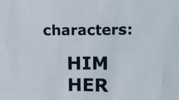 Piece of white paper with the words 'characters, him, her' typed on it