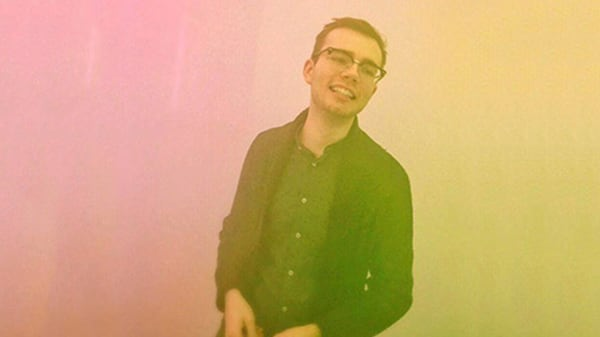 Photo of Ian Gustav, male UAL student, standing in a pink and yellow light