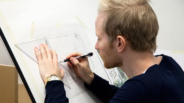 A blonde man drawing