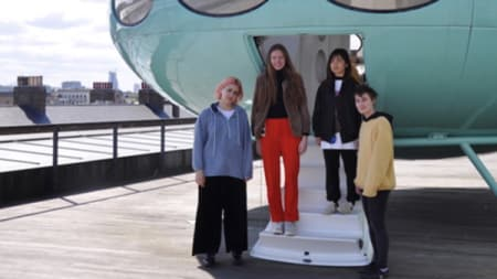 Three woman stood at the entrance of a Futuro House