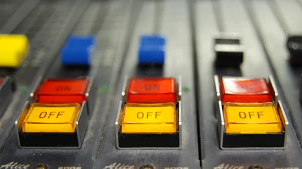 Close-up of mixing desk with red and yellow on off buttons in close