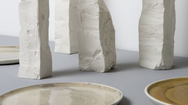 A series of tall ceramic objects on display