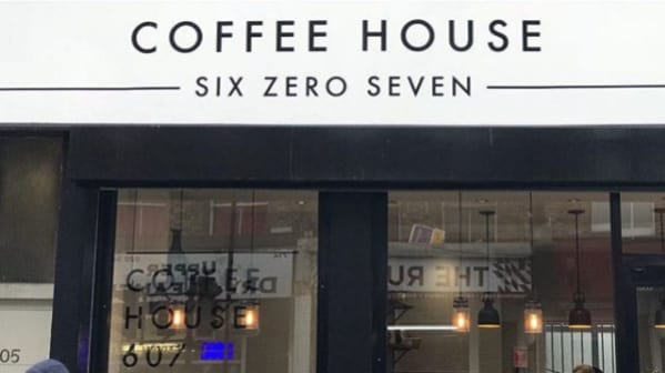 The facade of a coffee shop, 'Coffee House Six Zero Seven' is written above the door