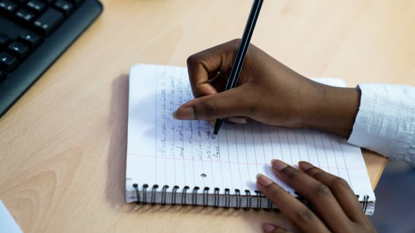 Students hands writing on notepad