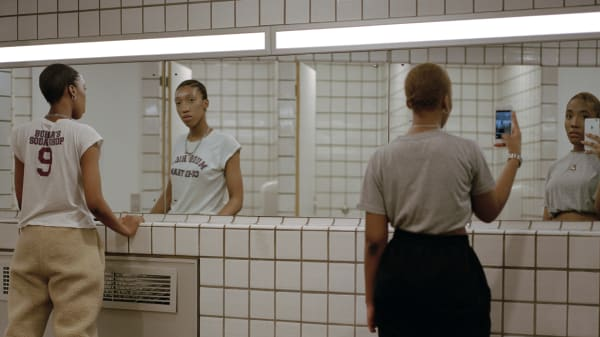 Two people looking into a mirror in a public toilet, one taking a selfie on a phone