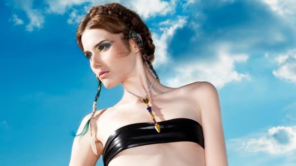 Woman wearing jewellery in front of a blue sky