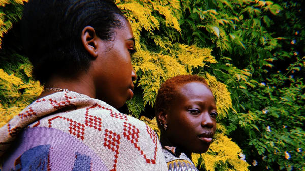 Two people stood with their back to the camera wearing thick woven garments