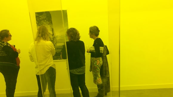 Photo of a group of people looking at a painting with a yellow wash over the picture
