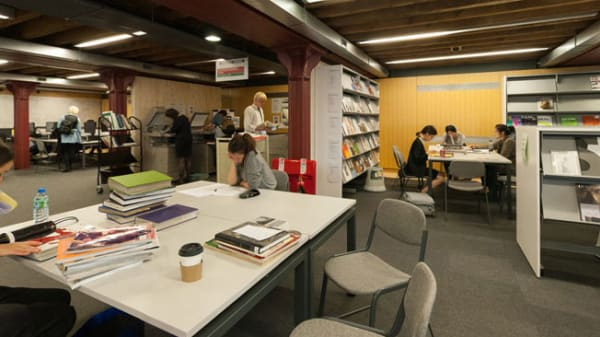 Students working at tables inside Central Saint Martins' Library