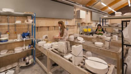 Students working with clay and ceramic pieces on display inside the Ceramics Workshop at Central Saint Martins