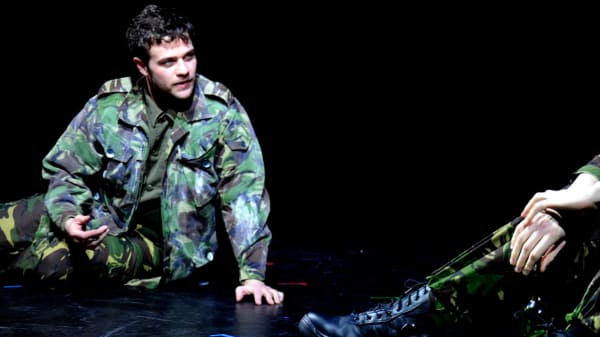 Two people dressed in green camouflage costumes talking and laughing on stage.
