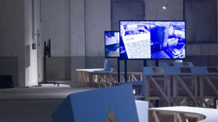A blue and grey photo of two display screens in an exhibition space