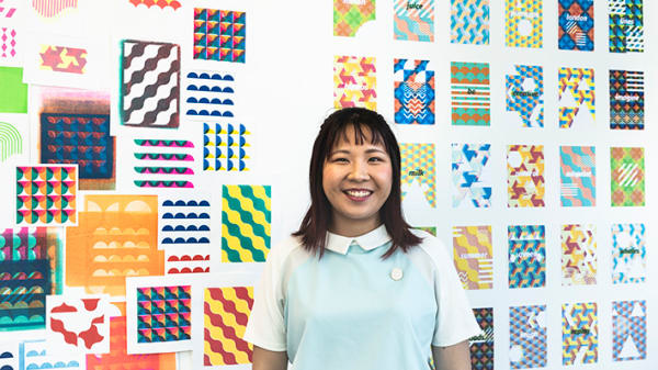 A smiling woman stands in front of a wall display of colourful prints.