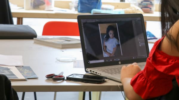 Student editing photo on laptop