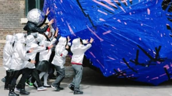children pushing a huge blue ball