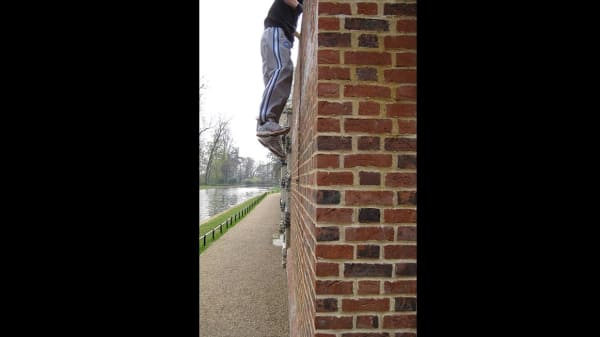 Someone climbing a brick wall