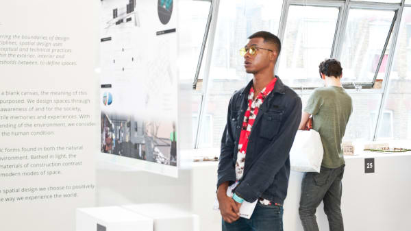 An LCC student looks at a piece of digital work during a degree show exhibition.