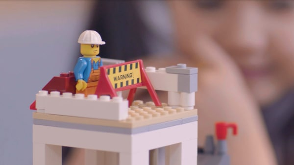Close up still from a film. Lego tower with a lego construction worker.
