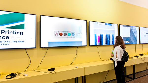 A woman stands in front of several screens mounted on a yellow wall.