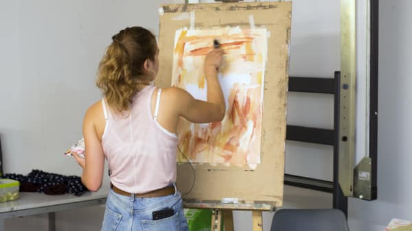 Student working on an abstract painting at and easel