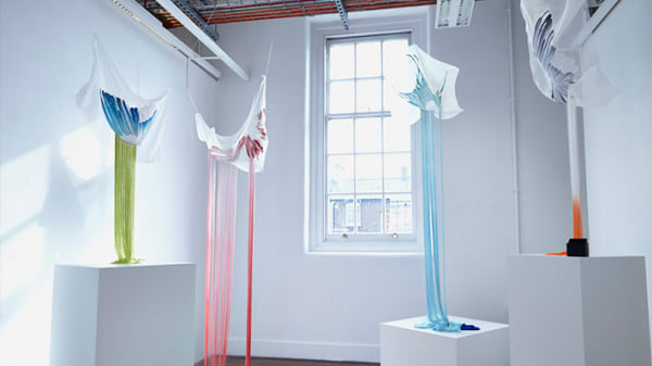 Photo of a white room with a large window with pieces of material hanging down