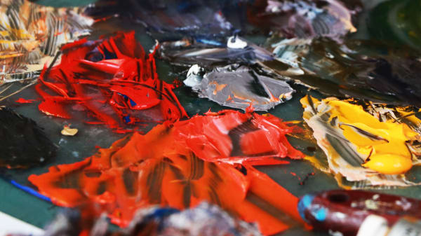 Paint on a painter's board, red, yellow, orange, black and green.