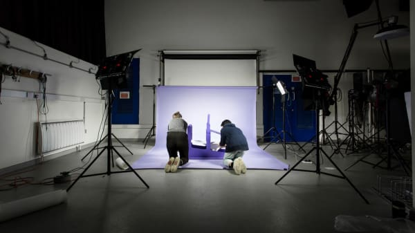 Two people in the London College of Communication photographic studio bent down on the floor