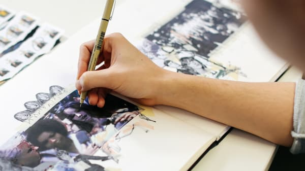 Close up shot of someone drawing on magazine pictures with a pen