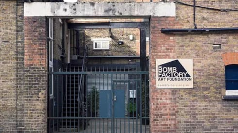 A brick building, a sign next to the door says 'Bomb Factory Art Foundation'
