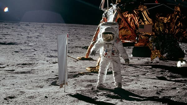 Astronaut in spacesuit stepping onto the moon. Apollo 11, moonlander in the background, with American flag. From Carl Grinter's film 'Thesis'.
