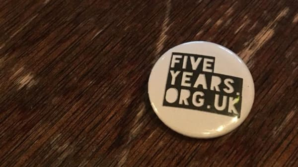 A badge which says 'fiveyearsgallery.org.uk' on top of a wooden table