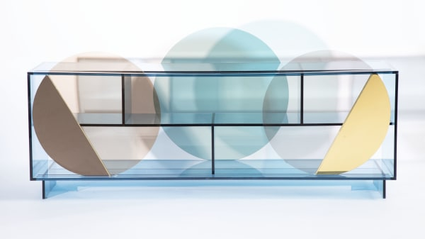 A perspex box with a series of perspex plates on display inside it. The plates are pastel blue, brown and cream with metallic detailing.