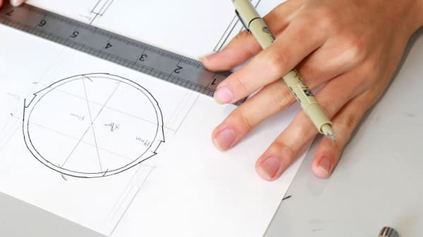 Person using ruler to draw a technical drawing. Visible in shot are a hand, ruler and circular drawing.