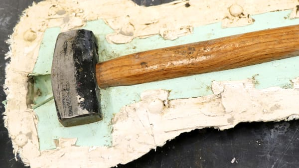 Mold of a hammer being cast.