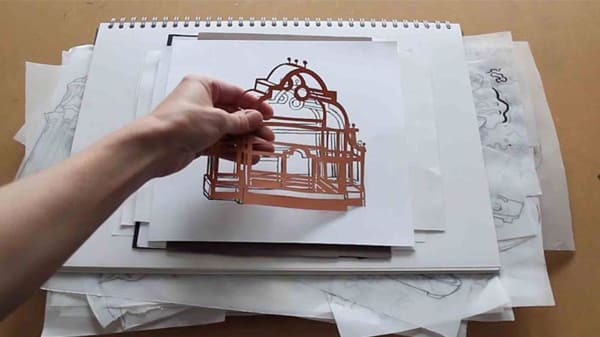 Cut outs being arranged on stacked sketchbooks