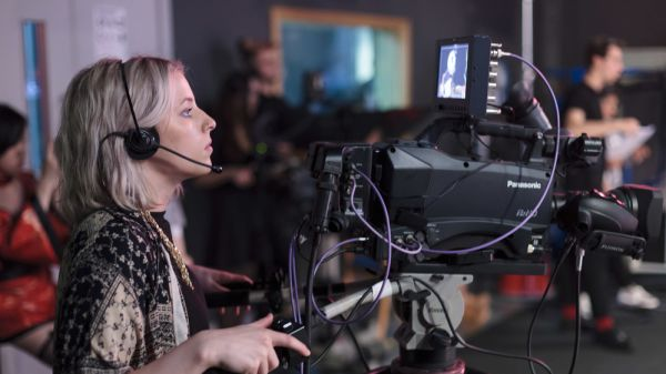 A young woman operating a television camera in a studio at London College of Communication