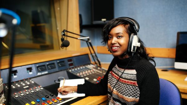 A journalism student at London College of Fashion wearing earphones in a broadcasting studio