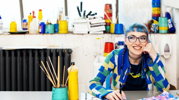 A smiling student with blue hair working in her studio