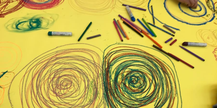 yellow paper shows hands scribbling colour pencil circles
