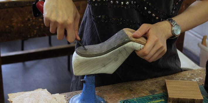 Person carving the sole of a shoe