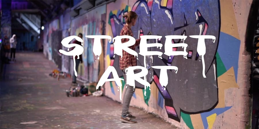 A still from a student film which reads 'Street Art' in white text against a background featuring a graffiti wall.