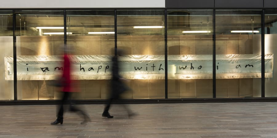 people are blurred walking past a long window, inside the window is a long fabric hanging that reads 'i am happy with who i am'
