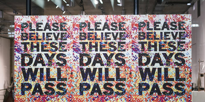 Three posters on a window which say 'These days will pass'