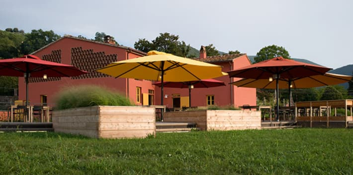 Photo of a red building in a grass field with large sun umbrellas outside