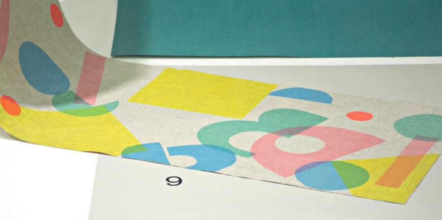 screen printed fabric with coloured circles lay on colour sheets in a window