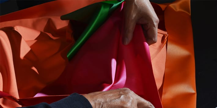 A pair of hands holding brightly coloured fabric