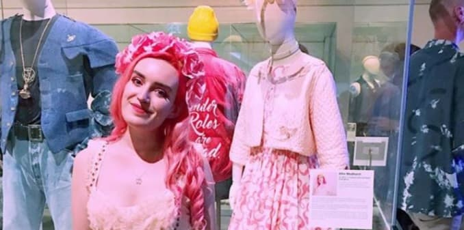 Young project team volunteer Ellie Medhurst in pink standing in front of mannequin dressed in her clothes donated to Queer Looks exhibition, Brighton Museum, 2018-19.
