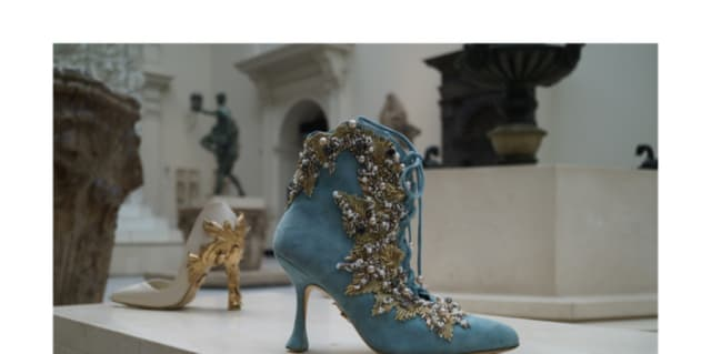 An ankle boot in turquoise suede with gold baroque column detailing on the heel